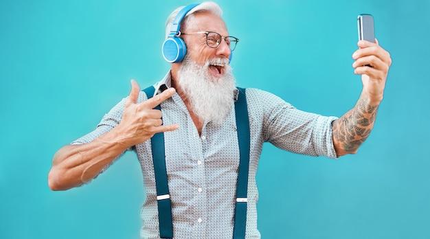 Hombre loco mayor que usa la aplicación de teléfono inteligente para crear una lista de reproducción con música rock - tipo de tatuaje moderno que se divierte con la tecnología del teléfono móvil - tecnología y concepto alegre de estilo de vida para personas mayores - centrarse en la cara Foto Premium