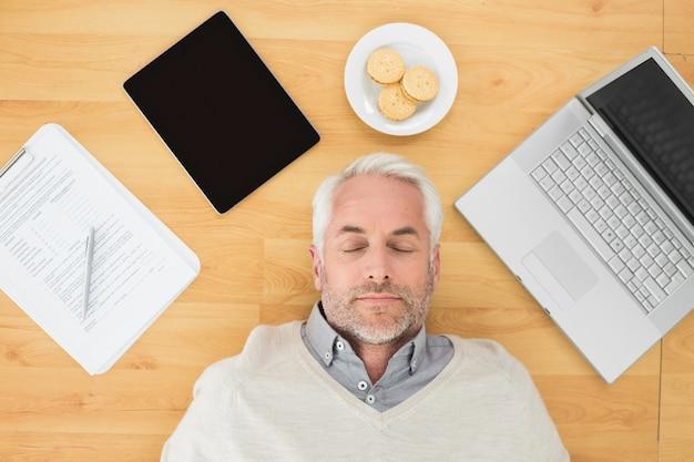 Hombre maduro durmiendo con electrónica y galletas en el piso de parquet Foto Premium