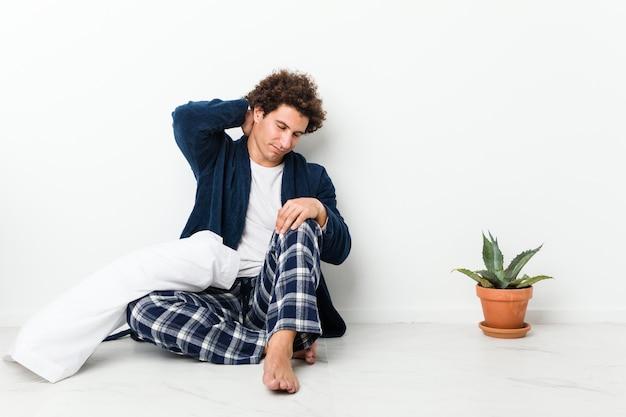 Hombre maduro vistiendo pijama sentado en el piso de la casa sufriendo dolor de cuello debido al estilo de vida sedentario. Foto Premium