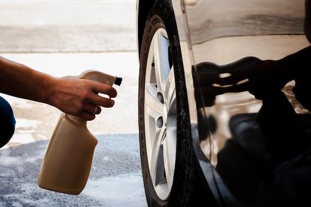 Hombre mano rociando una rueda de coche Foto Premium