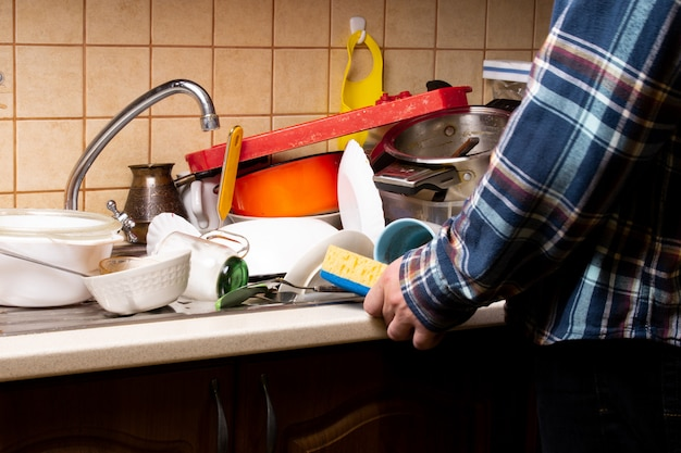 Hombre de la mano con una toallita cerca de muchos platos sucios en el fregadero de la cocina que desea lavar Foto Premium