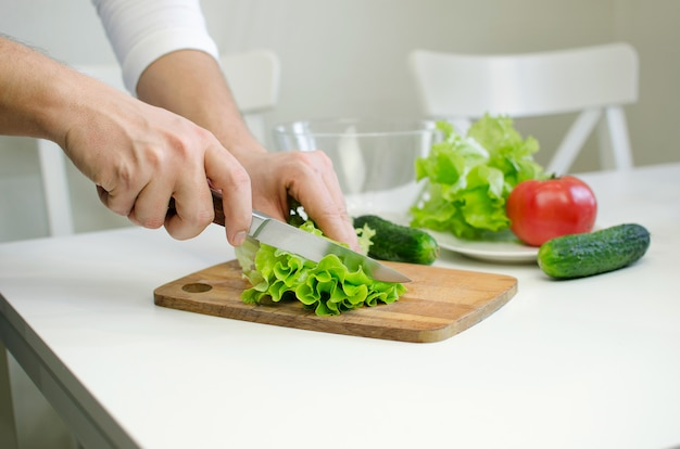Hombre manos prepairing ensalada. corte de salat. Foto Premium