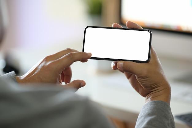 Hombre manos sosteniendo pantalla móvil smartphone en blanco en la oficina Foto Premium