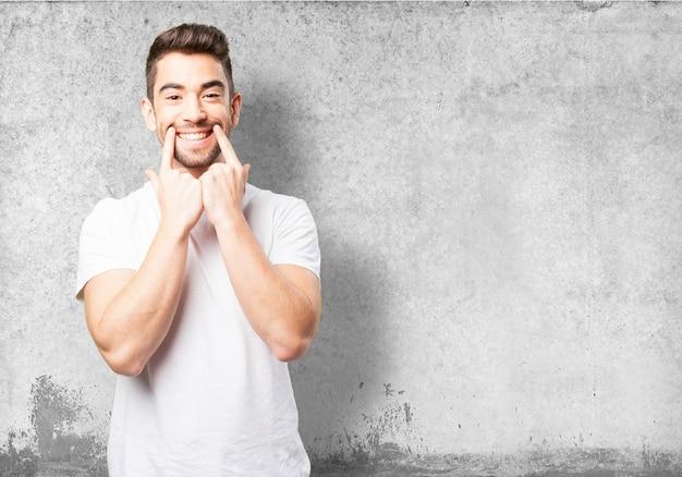 Hombre marcando su sonrisa con dos dedos Foto Gratis