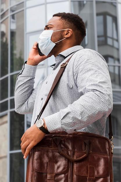 Hombre con máscara de camino al trabajo durante la pandemia y hablando por teléfono Foto gratis