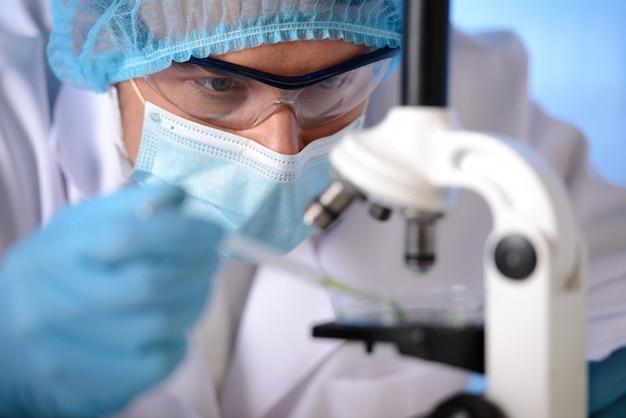Un hombre con máscara y gafas está experimentando con un microscopio. Foto Premium