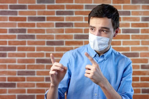 Hombre de máscara médica blanca apuntando con las manos Foto gratis