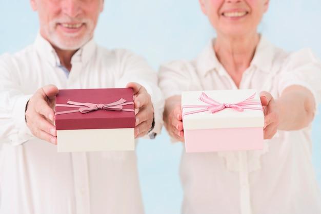 Hombre mayor alegre y mujer que dan la caja de regalo Foto gratis