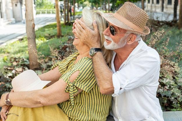Hombre mayor cubriendo los ojos de la mujer con sus palmas Foto gratis