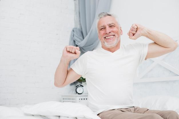 Hombre mayor despertándose en la cama Foto gratis