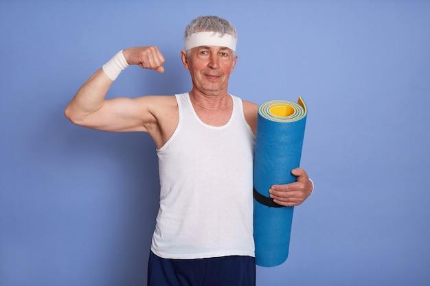 Hombre mayor enérgico tiene entrenamiento físico, sosteniendo una estera de yoga, mostrando bíceps y su poder Foto gratis