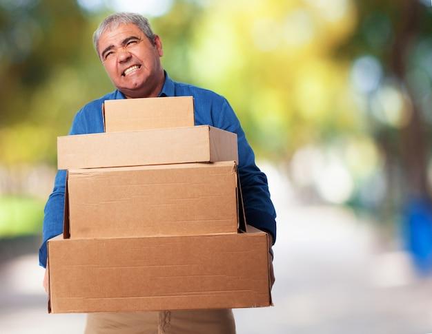 Hombre mayor haciendo esfuerzo mientras carga cajas de cartón Foto gratis