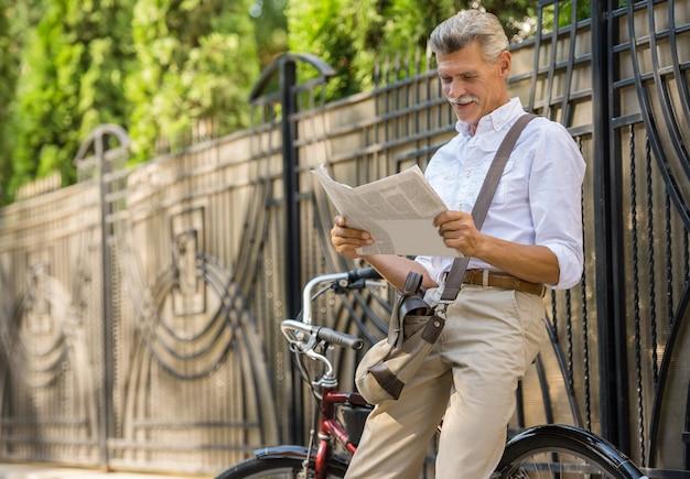 El hombre mayor está leyendo el periódico mientras que se sienta en la bicicleta. Foto Premium