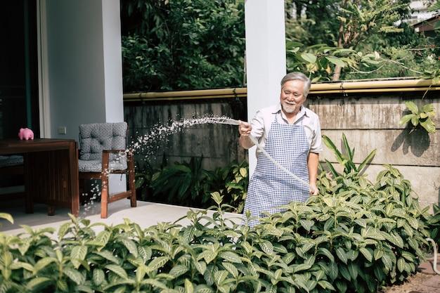 Hombre mayor plantar un árbol en casa Foto gratis