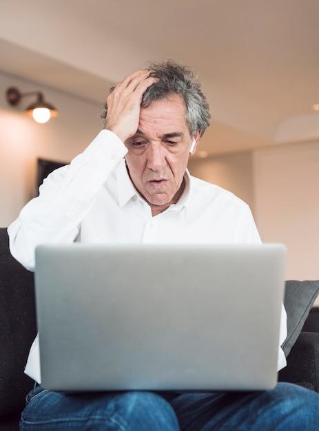 Hombre mayor preocupado que se sienta en el sofá que mira la computadora portátil Foto gratis