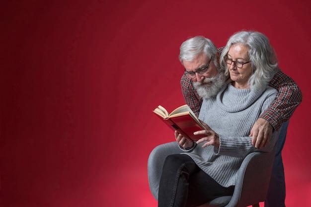 Hombre mayor que abraza a su esposa que lee el libro contra fondo rojo Foto gratis
