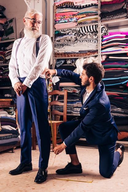 Hombre mayor que mira al diseñador de moda de sexo masculino que toma la medida de sus bragas en la tienda Foto gratis