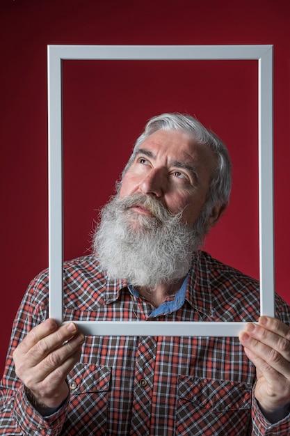 Hombre mayor que mira para arriba que lleva a cabo el marco blanco de la frontera delante de su cara contra el contexto rojo Foto gratis