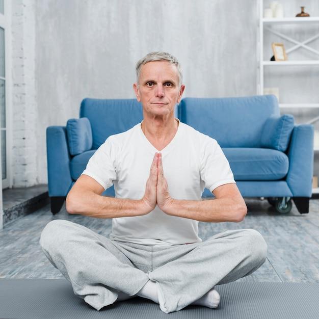 Hombre mayor que se sienta en la estera de la yoga que hace gesto de rogación Foto gratis