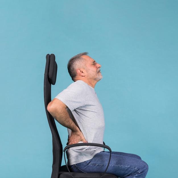 Hombre mayor que se sienta en la silla que tiene dolor de espalda en fondo azul Foto gratis