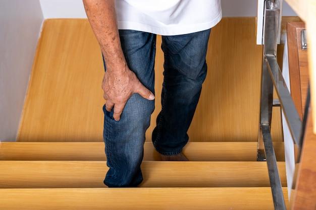 Hombre mayor que sube las escaleras y se toca la rodilla por el dolor de la artritis. cuidado de la salud. día mundial de la tercera edad. Foto Premium