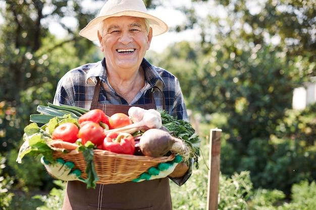 Hombre mayor que trabaja en el campo con una caja de verduras Foto gratis