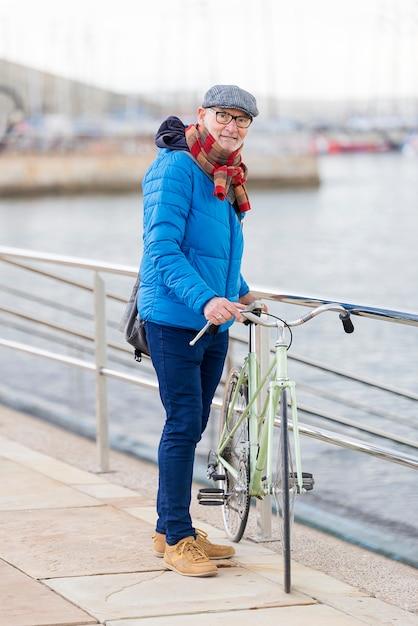 Hombre mayor del retrato que camina con su bicicleta en la calle Foto Premium