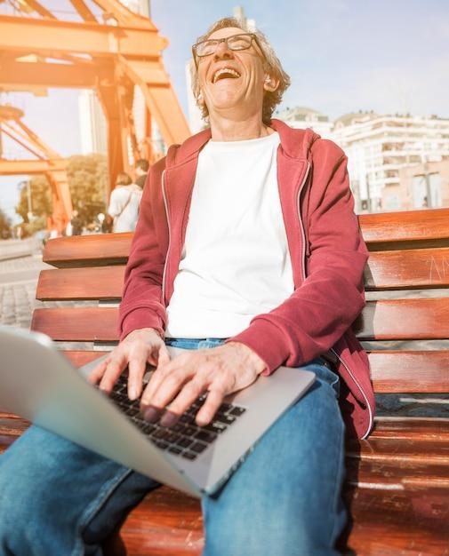 Hombre mayor de risa que se sienta en banco con un ordenador portátil abierto en su regazo Foto gratis