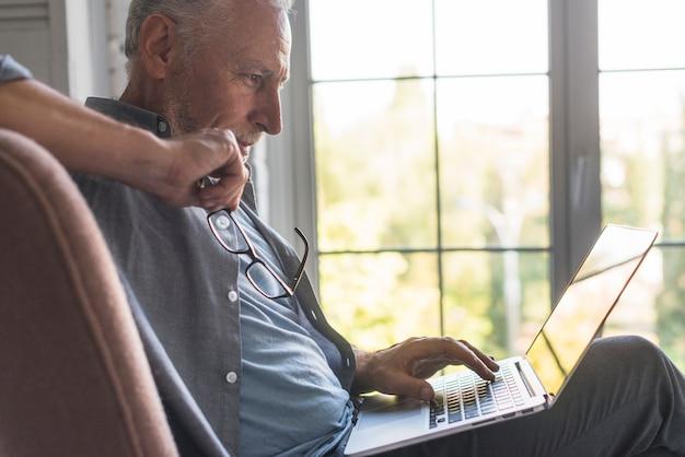 Hombre mayor serio que usa la computadora portátil en casa Foto Premium