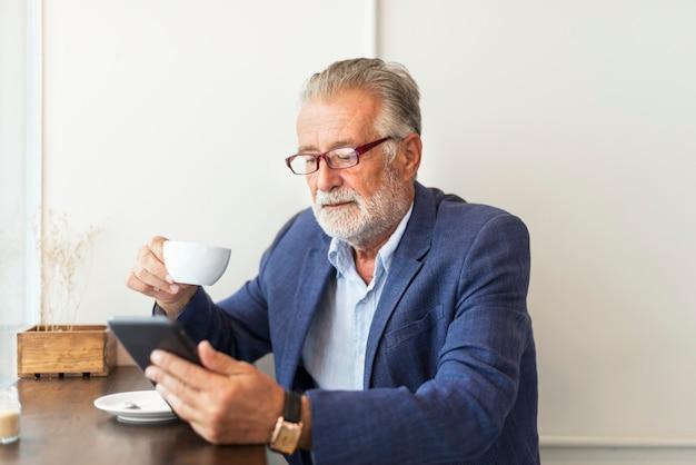 Hombre mayor está utilizando tableta digital Foto Premium