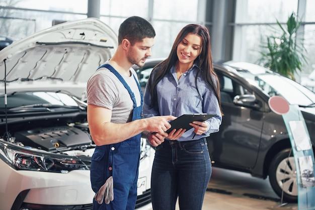 Un hombre mecánico y una clienta discutiendo reparaciones hechas a su vehículo Foto gratis