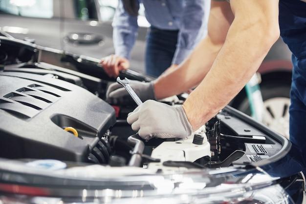 Un hombre mecánico y una mujer cliente miran el capó del automóvil y discuten las reparaciones Foto gratis
