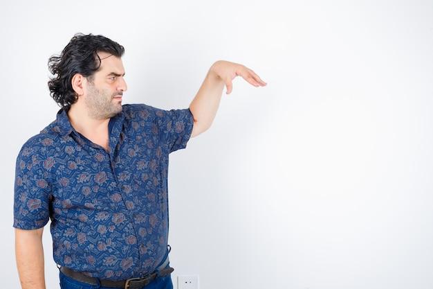 Hombre de mediana edad en camisa fingiendo sostener algo y mirando serio, vista frontal. Foto gratis