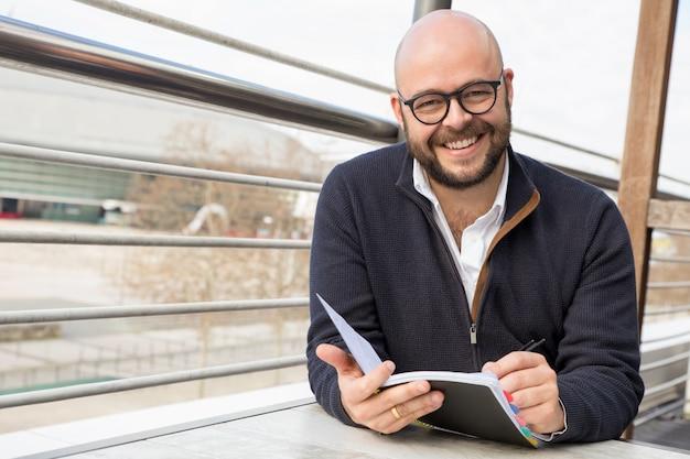 Hombre de mediana edad feliz que hace notas en café de la calle Foto gratis