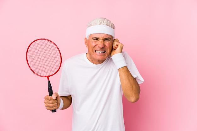 Hombre de mediana edad jugando bádminton aislado cubriendo las orejas con las manos. Foto Premium