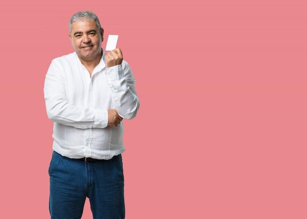 Hombre de mediana edad sonriendo confiado, ofreciendo una tarjeta de visita, tiene un negocio próspero Foto Premium