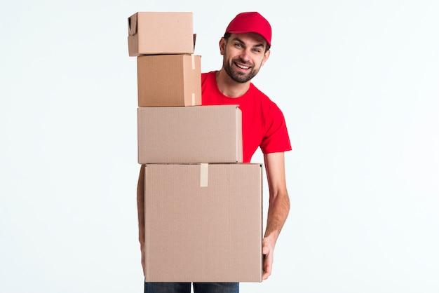 Hombre mensajero con pila de cajas de paquetería Foto gratis