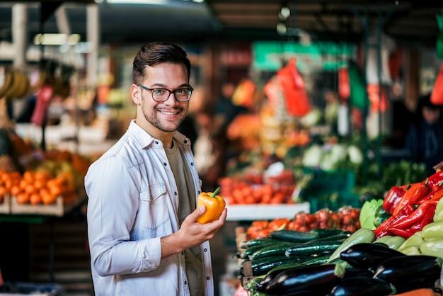 Hombre milenario hermoso que compra verduras frescas en el mercado callejero. Foto Premium
