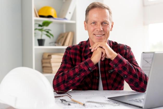 Hombre mirando a la cámara en su oficina Foto gratis