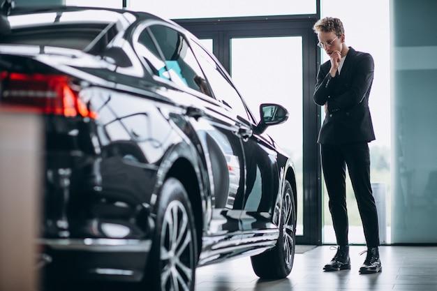 Hombre mirando un carro y pensando en una compra. Foto gratis