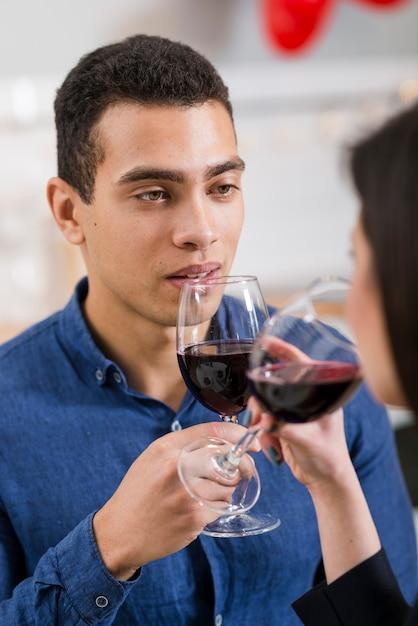 Hombre mirando a su novia mientras sostiene una copa de vino Foto gratis