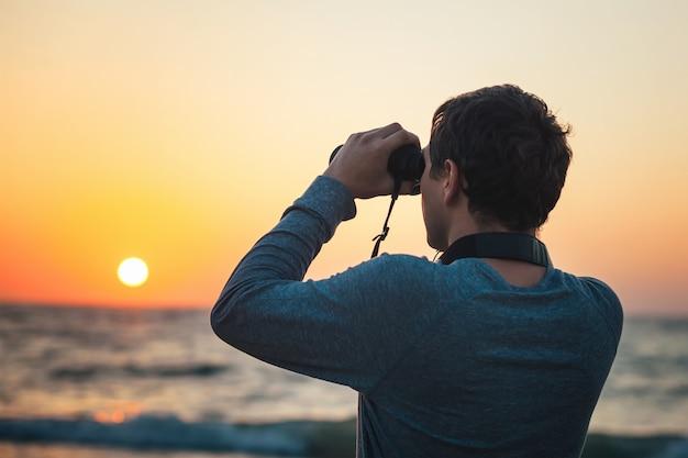 Un hombre mirando a través de binoculares de pie en la playa. Foto Premium