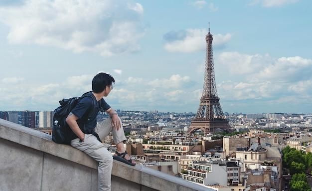 Un hombre con mochila mirando la torre eiffel, famoso monumento y destino de viaje en parís, francia Foto Premium