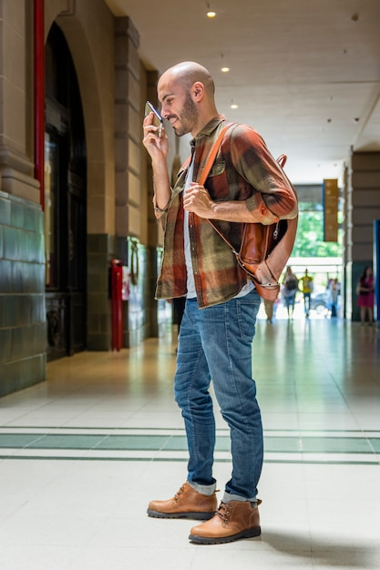 Hombre con mochila con móvil Foto gratis