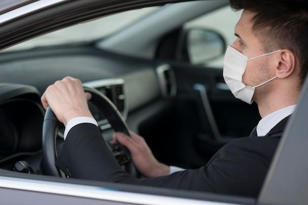 Hombre moderno en auto con máscara Foto Premium