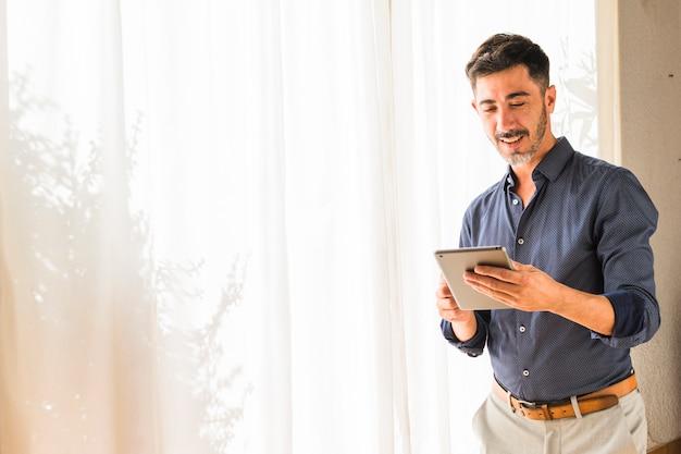 Hombre moderno sonriente que se coloca delante de la cortina blanca usando la tableta digital Foto gratis