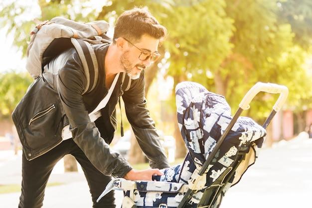 Hombre moderno sonriente con su mochila que cuida a su bebé en el parque Foto gratis