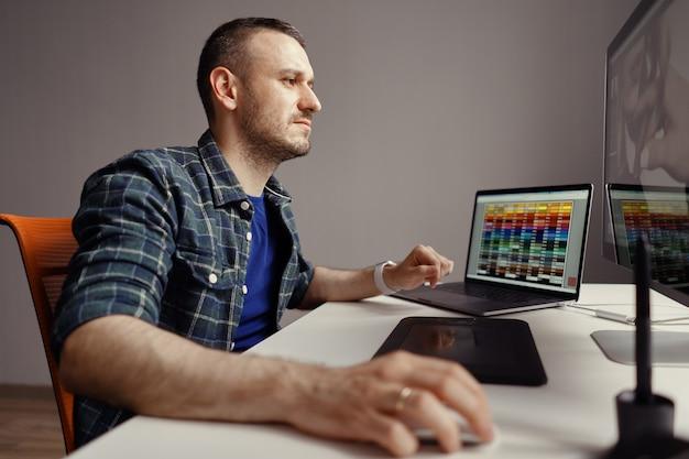 Hombre moderno trabajando remotamente en una computadora desde la oficina en casa Foto gratis