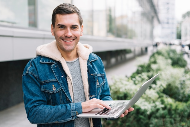 Hombre moderno usando portátil en entorno urbano Foto gratis