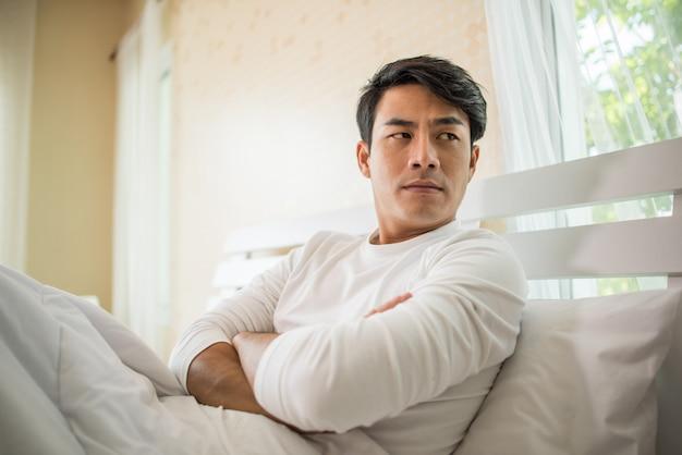 Hombre molesto que tiene problemas para sentarse en la cama después de discutir con su novia Foto gratis